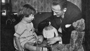 Photo de A. A. Milne jouant avec son fils Christopher Robin, l'ourson Winnie, et un pingouin. Photo credit : Culture Club/Getty Images